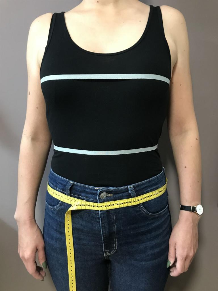 Ziehen Sie Ihre Reitjeans an und stellen Sie sich gerade hin. Legen Sie das Maßband unterhalb der Gürtelschlaufen an und messen möglichst straff rundherum.