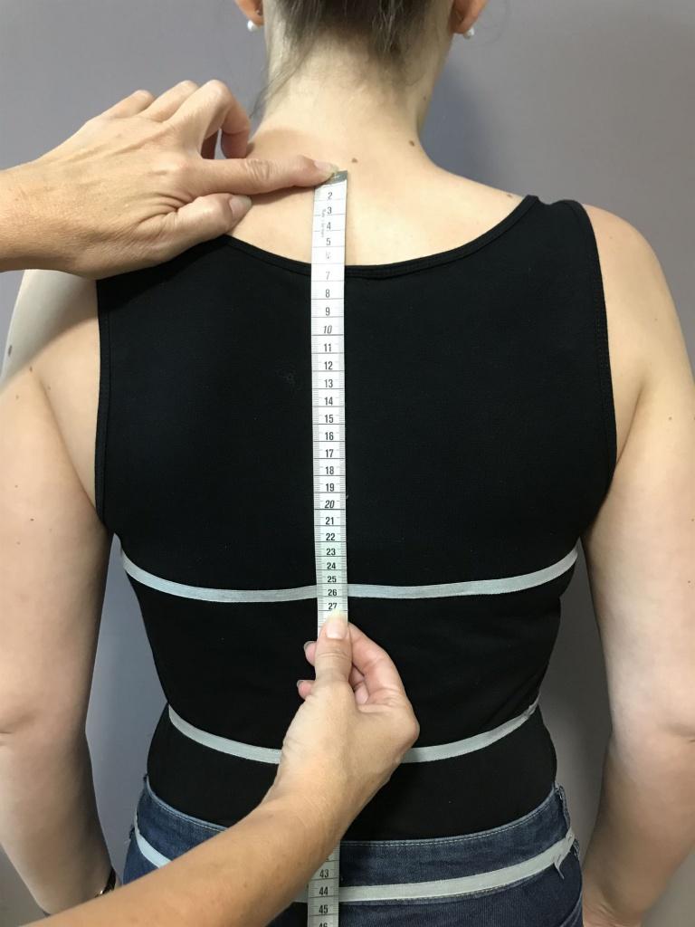 Legen Sie das Maßband am ersten Halswirbel an und messen bis zu der Schnur an der Taille.