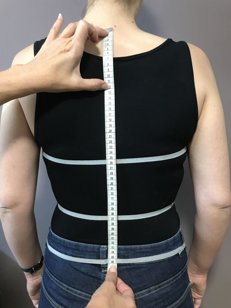 Legen Sie das Maßband am ersten Halswirbel an und messen zur gewünschten Länge des Outfits.