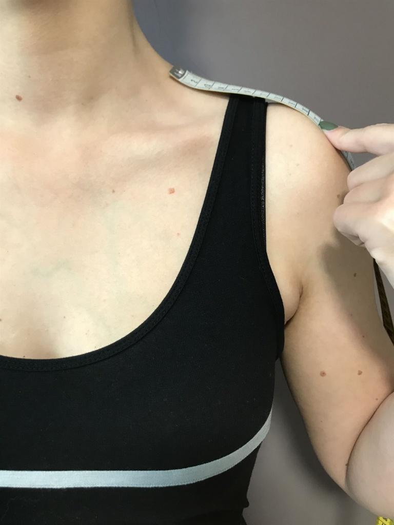 Legen Sie das Maßband am Halsansatz an und messen bis zur Schulterspitze.